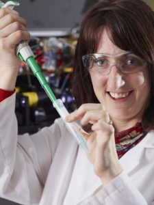 Female scientist holds vial and is smiling at the camera. She is wearing a lab coat and safety googles