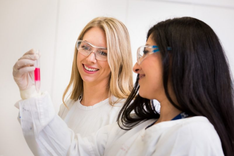 Two smiling women scientists in white coats and safety glasses inspecting a vial containing a pink substance.