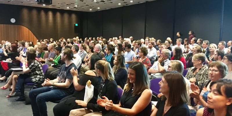Photograph of a Monday Lunch Live auditorium clapping and smiling