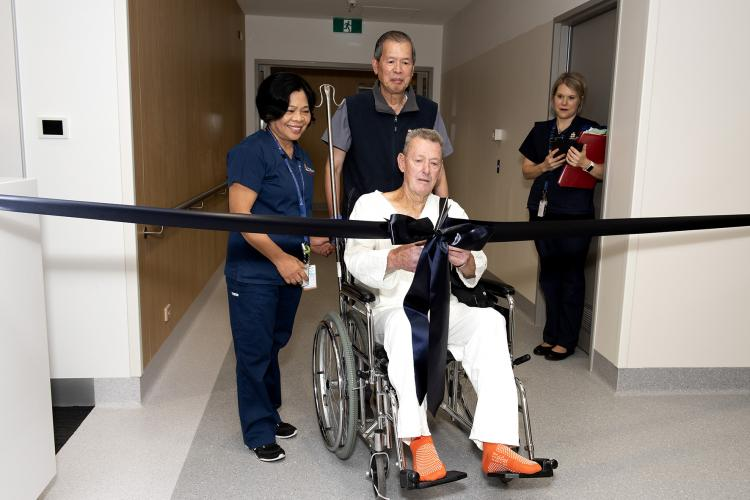 Kelton Young sits in a wheel chair and cuts the ribbon to the new ward.